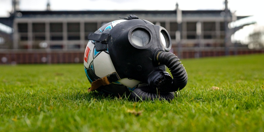 Ein Fußball mit Gasmaske vor dem Rheinenergie Stadion.