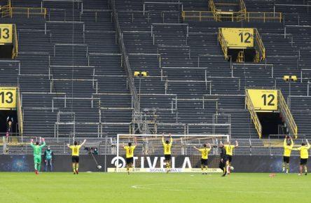Die Spieler des BVB feiern ihren Derbysieg vor der leeren Südtribüne.